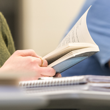 Photo of a student's hands holding an open book