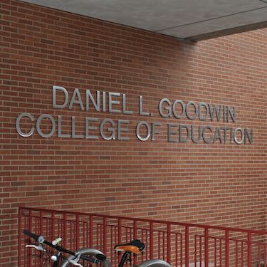 Photo of the exterior sign of the Daniel L. Goodwin College of Education in silver against brown brick