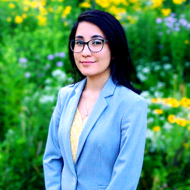 Obsmara Ulloa wearing a light blue suit jacket stands outdoors with flowers and greenery in the background