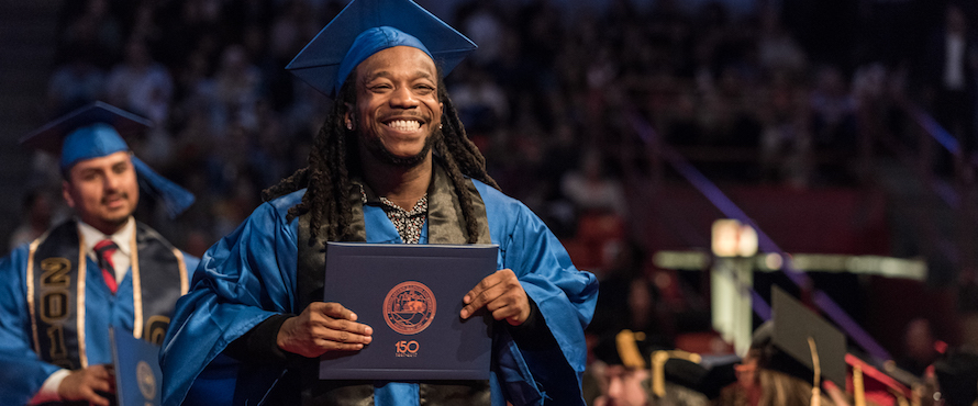 A smiling male graduate wearing blue regalia holds his diploma