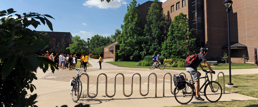 Two bicyclists ride on Northeastern's campus near the Ronald Williams Library. A tour group is in the background.