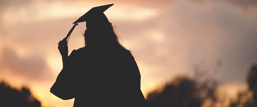 A female graduate wearing gown and mortarboard in silhouette against a sunset sky