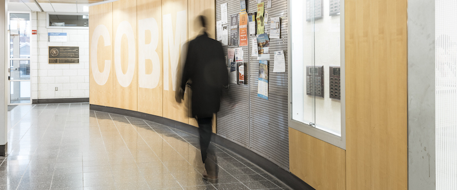 A person walks in the hallways of the College of Business and Management
