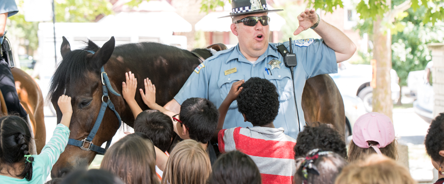 A Chicago Police Officer answers questions while standing in front of a police horse.