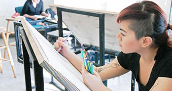 Female student drawing in art class