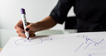 A student drawing on a whiteboard.