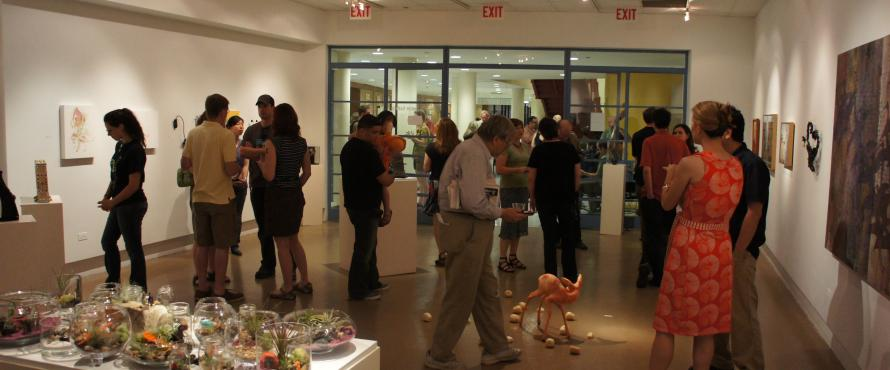 People mingle in the gallery during an opening.