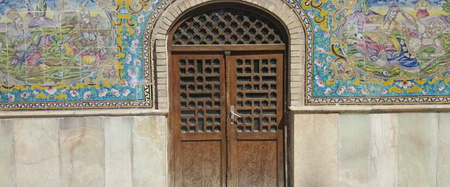 A carved wooden double door surrounded by painted tiles at a location in Iran