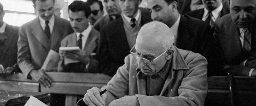 Mohammad Mossadegh seated at a table writing