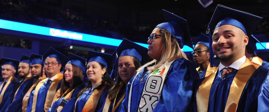 Students smile during Commencement.
