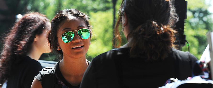 closeup of woman wearing aviator sunglasses, talking outdoors with a friend