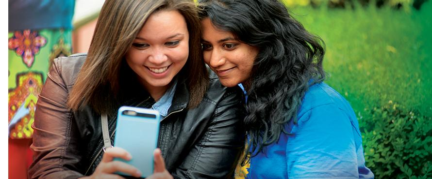 Two female students sit closely together to take a selfie photo on a mobile phone