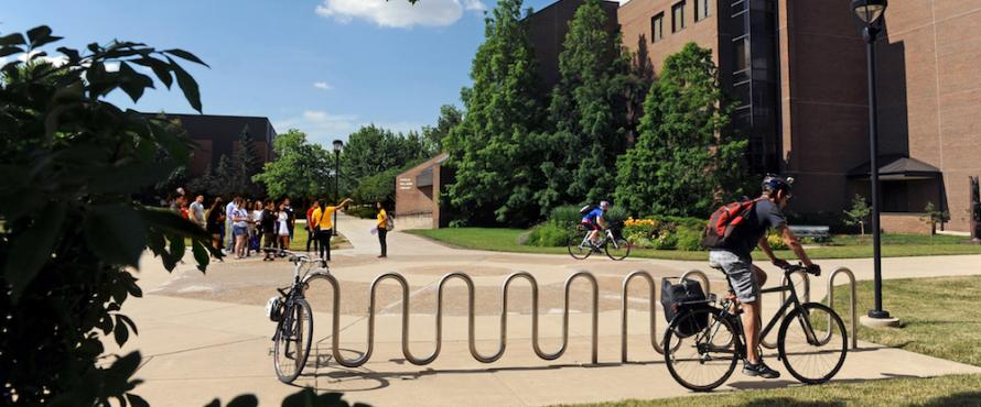 A man on a bike rides past and people walk the sunny outdoor paths of the University Commons