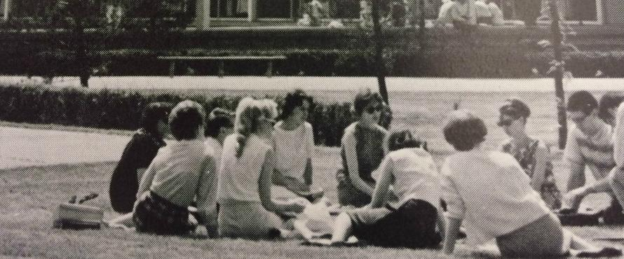 Members of the Class of 1967 sit in a circle on the lawn outside of the Sachs Building