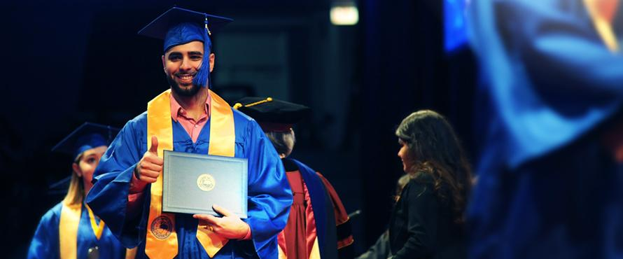 At Commencement, graduate walking the stage with diploma cover in hand.