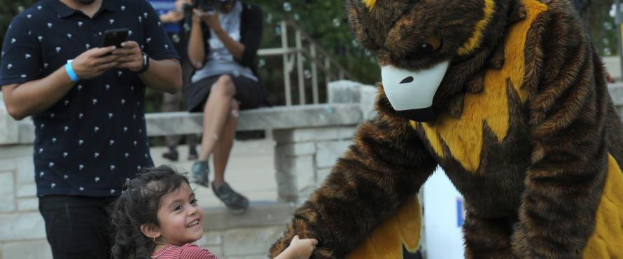 A child shakes Goldie's hand at NEIU Weekend