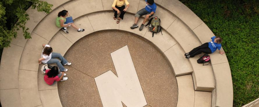 Students sitting in a rotunda outside. The NEIU N is the middle of the rotunda