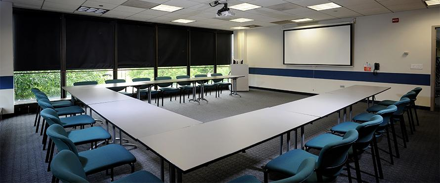 A conference room with a table and chairs.