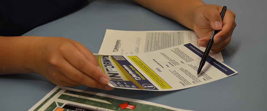 Close up shot of hands and informational handouts.