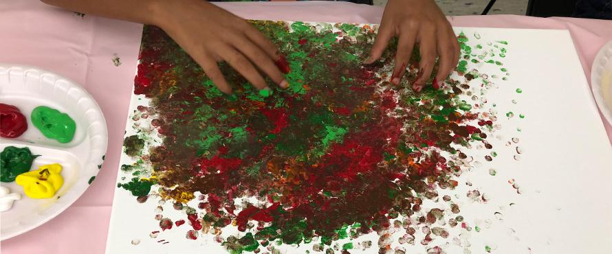 A hand is shown over red and green glitter.