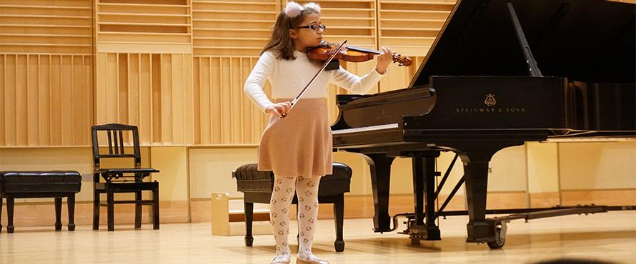 A student plays violin on the Recital Hall stage.