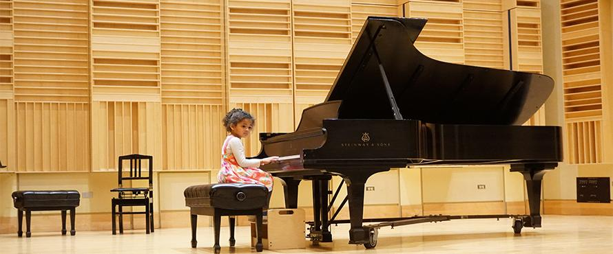 A student plays a grand piano in the Recital Hall.