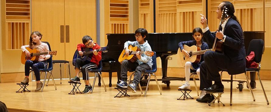 Students play the guitar on the Recital Hall stage.