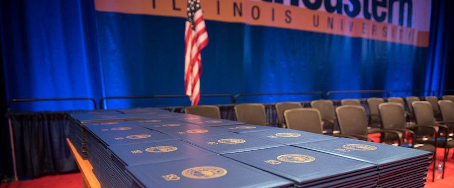 A stack of diplomas on a table with the United States flag and Northeastern Illinois University logo in the background
