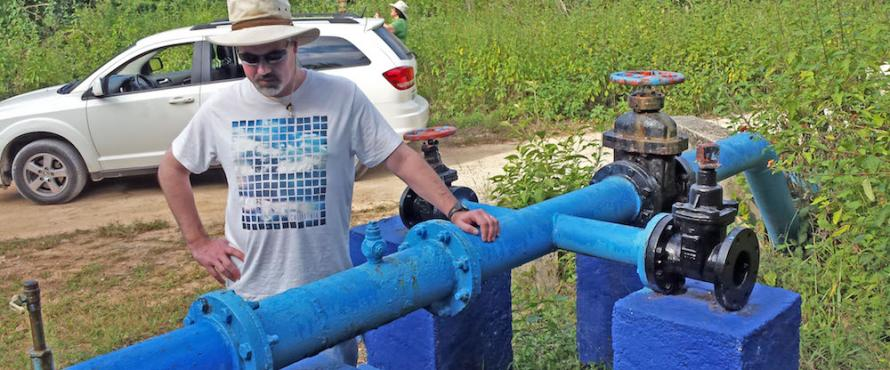 Earth Science Department Coordinator Ken Voglesonger examines one of the pumps that supply groundwater to the city.