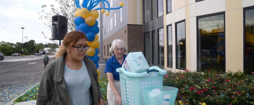 President Sharon Hahs helps freshman Luz Colin move into The Nest.