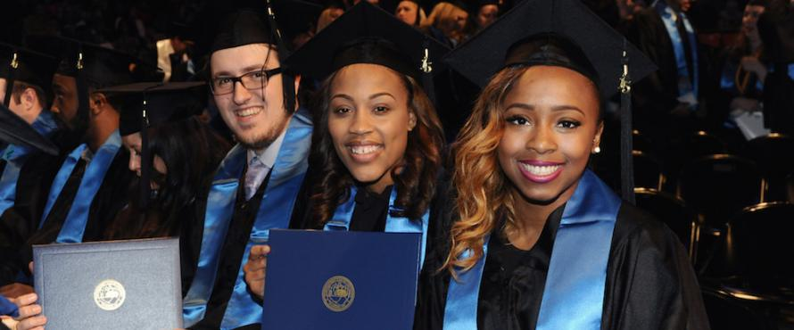 From left to right, a male and two female graduates holding diplomas and smiling