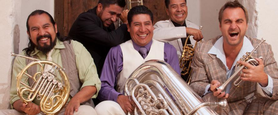 M5 Mexican Brass band members laughing and holding brass musical instruments
