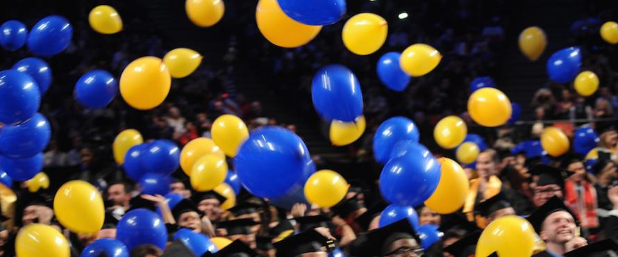 Blue and yellow balloons fall from the rafters at the UIC Pavilion during NEIU Commencement