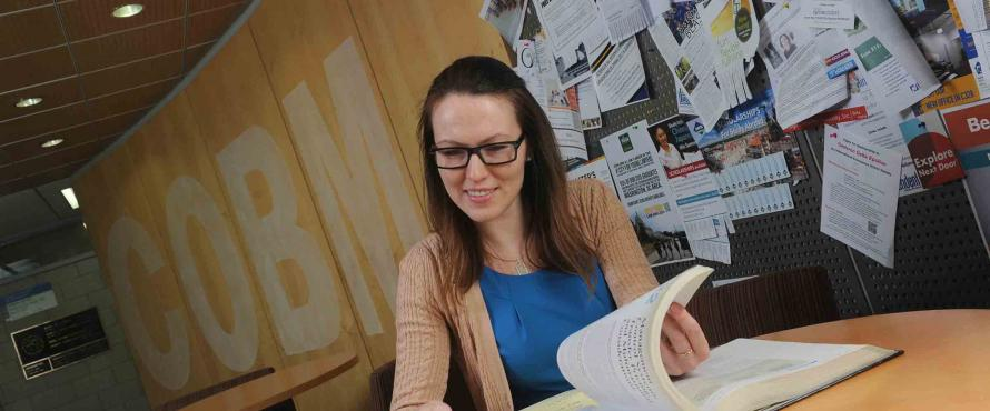 Accounting student Anna Davydova sitting at a table and turning the pages of a book