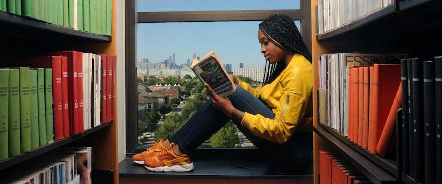 A female student reads a book while seated on the interior ledge of a window on the Carruther Center building.