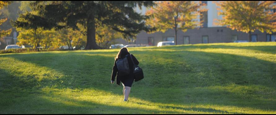 A woman is seen from behind as she walks across the grassy area east of The Nest