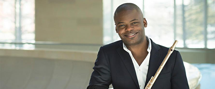 Flutist Demarre McGill holds a flute and poses indoors in front of windows