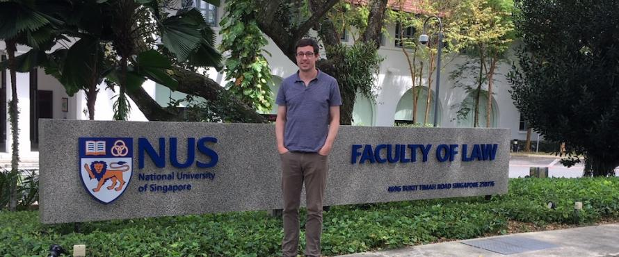 Assistant Professor of Business Law Richard Kilpatrick stands outdoors in front of National University of Singapore signage