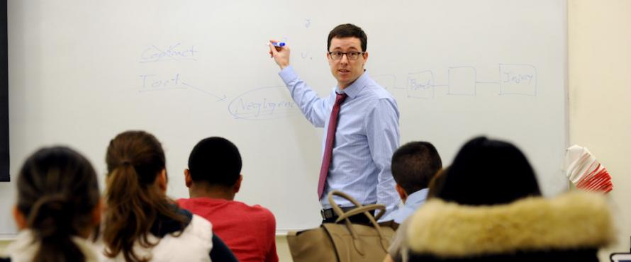 Assistant Professor of Business Law Richard Kilpatrick standing in front of a whiteboard in a classroom of students