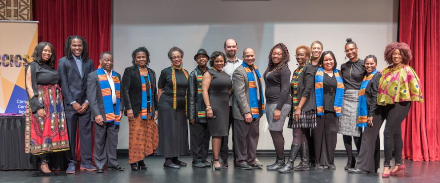 Sixteen people pose as a group on a stage at Carruthers Center for Inner City Studies