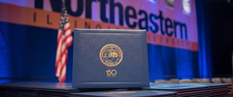 A diploma cover on display at December 2017 Commencement with an American flag and a branded Northeastern banner in the background