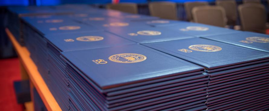 Stacks of diploma covers sitting on a table at a Commencement ceremony