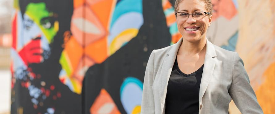 Carruthers Center Director Andrea Evans stands in front of a colorful mural