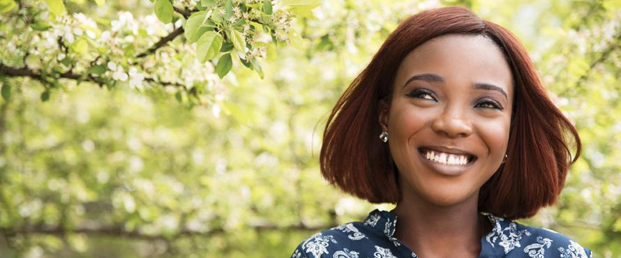 Alumna Margo Odiko-Pim smiling outdoors with trees in the background
