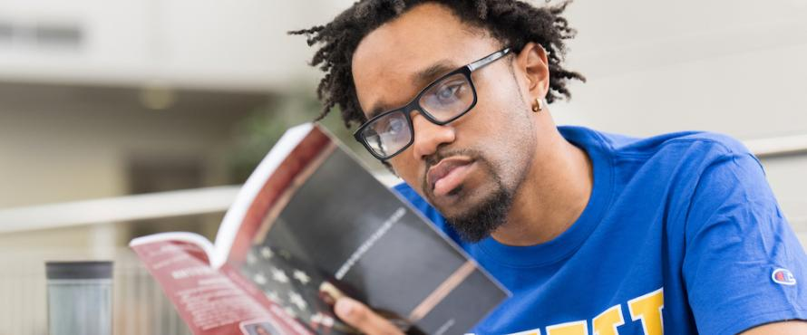 Graduate student Byron Terry reading a book