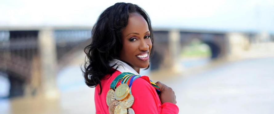 Jackie Joyner-Kersee looks back over her shoulder over which is draped her many Olympic medals