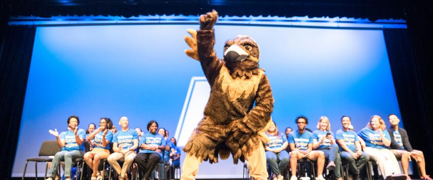NEIU mascot Goldie the Golden Eagle raising a wing on the Auditorium stage