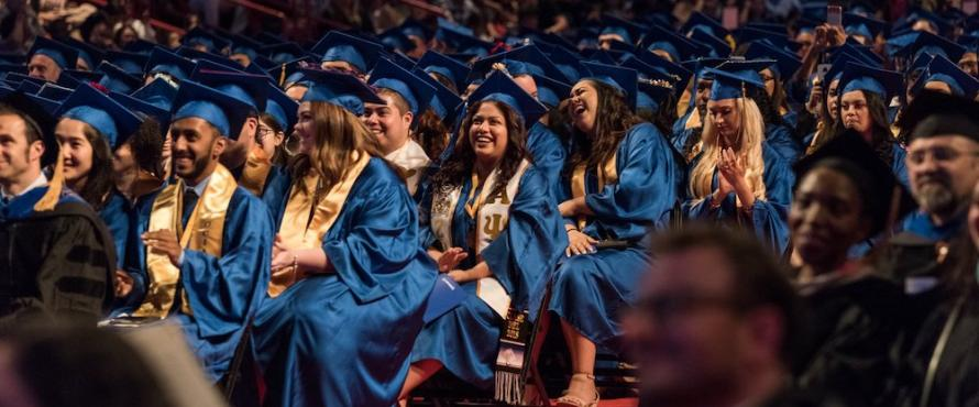 Graduates dressed in blue robes seated at a Commencement ceremony