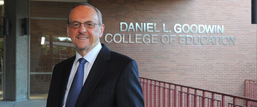 Daniel L. Goodwin stands outside of Lech Walesa Hall in front of a wall that reads Daniel L. Goodwin College of Education