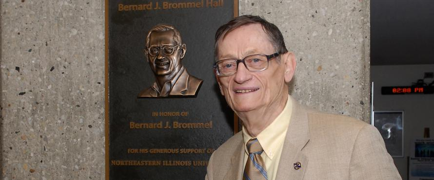 Bernard J. Brommel stands in front of the plaque in Bernard Brommel Hall that bears his name and likeness